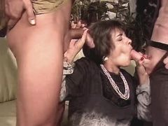 Aged mature sucks two cocks in orgy